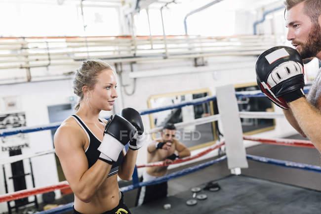 Kaukasische Boxerin beim Sparring mit Trainer — Stockfoto