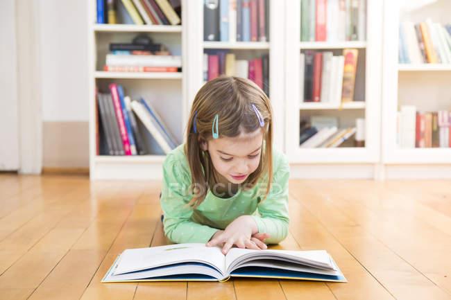 Petite fille allongée sur le sol et lisant un livre — Photo de stock