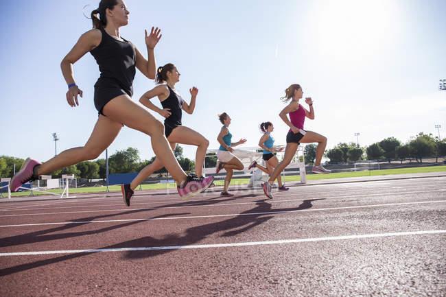 Female runners on tartan track at stadium — Stock Photo