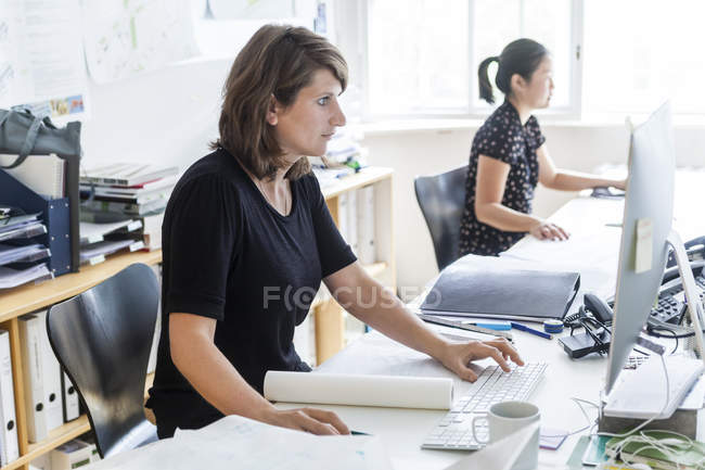 Two female architects working with computers in office — Stock Photo