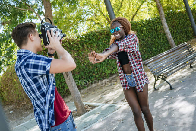 Young man filming his girlfriend with an old-fashioned camera — Stock Photo