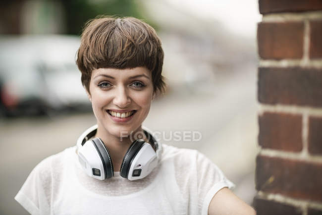 Portrait of happy young woman with short brown hair and white headphones — Stock Photo