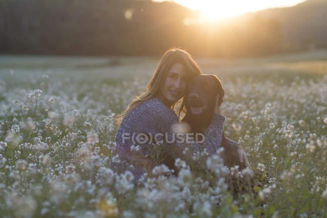 Mujer joven y perro sentado en el campo de flores en el crepúsculo - foto de stock