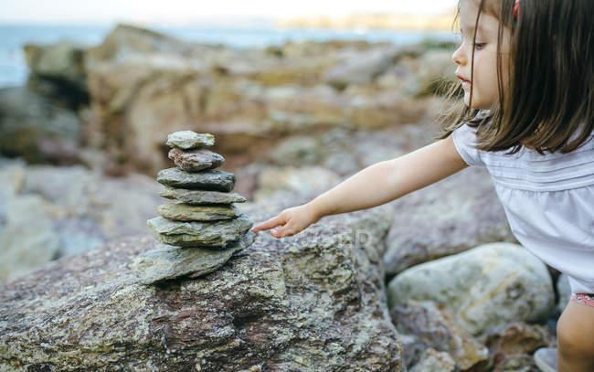 Menina com pilha de pedras na costa rochosa — Fotografia de Stock