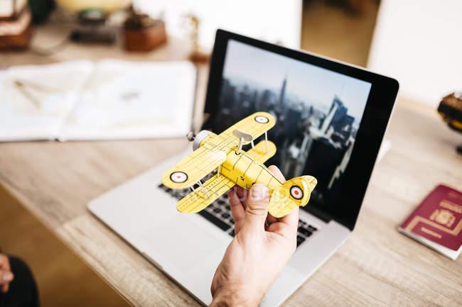 Hombre que sostiene el avión de juguete delante de ordenador portátil - foto de stock