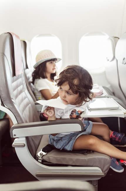 Dos niñas volando en avión, jugando con avión de papel - foto de stock