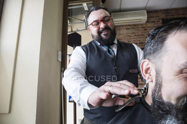Barbiere tagliare i capelli di un uomo utilizzando un tagliacapelli vintage mano operato — Foto stock