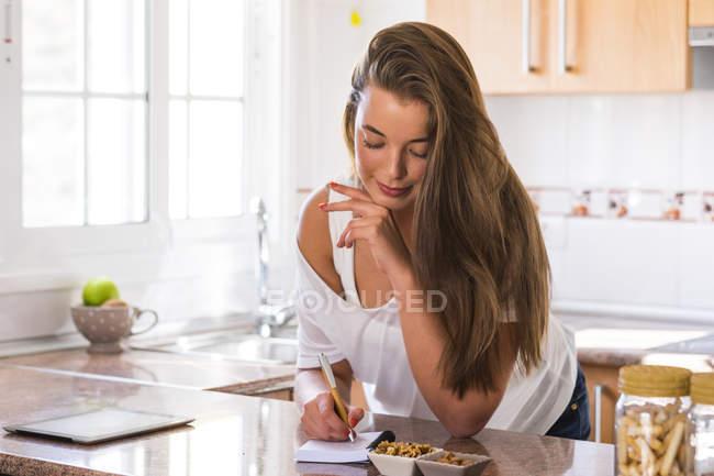 Mulher jovem, escrevendo no bloco de notas na cozinha — Fotografia de Stock