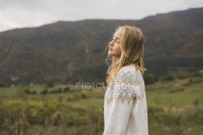 Jeune femme portant pull debout dans la nature — Photo de stock