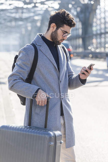 Homme d'affaires avec des bagages à l'aide de téléphone portable à l'extérieur — Photo de stock