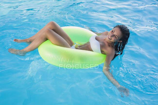 Jovem mulher flutuando na água na piscina — Fotografia de Stock
