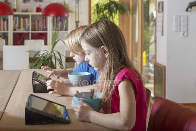 Garçon et fille à l'aide de comprimés à la table du petit déjeuner — Photo de stock