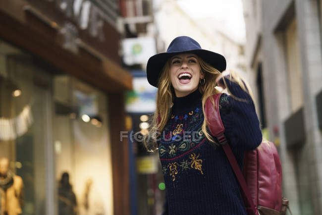 Portrait of fashionable young woman with hat and backpack — Stock Photo