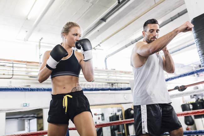Kaukasische Boxerin übt mit Trainer — Stockfoto