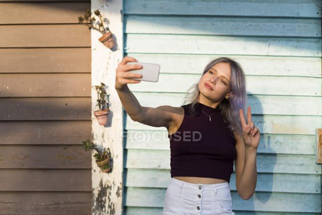 Молодая женщина с окрашенными волосами, принимая selfie — стоковое фото