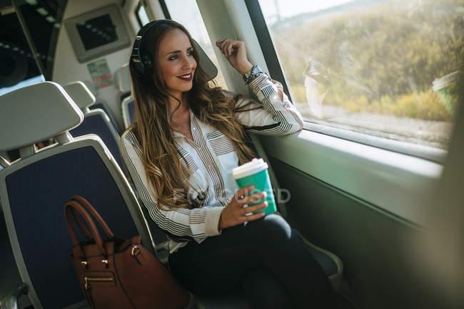 Femme dans un train écoutant de la musique avec un casque et buvant du café — Photo de stock