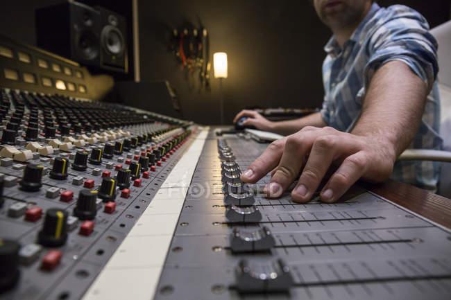 Рука человека, работающего в комнате управления студии звукозаписи — стоковое фото