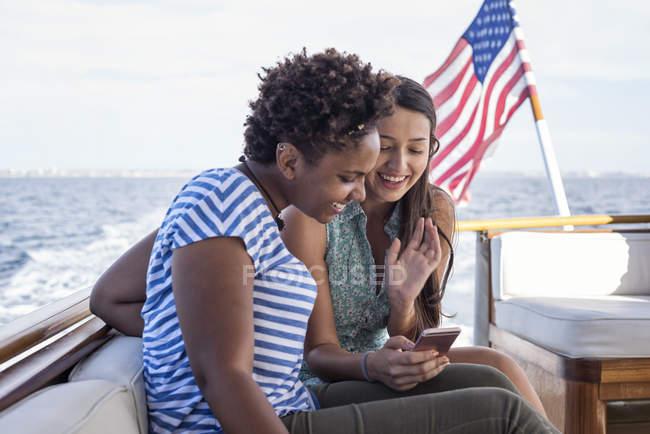 Zwei glückliche junge Frauen, die auf einem Boot sitzen und ihr Handy teilen — Stockfoto