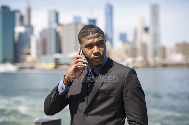 USA, Brooklyn, ritratto di un uomo d'affari al telefono davanti allo skyline di Manhattan — Foto stock