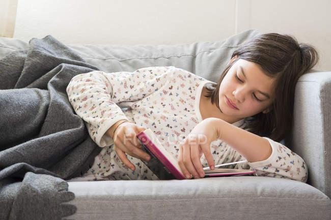 Fille couchée sur le canapé et lisant un livre — Photo de stock