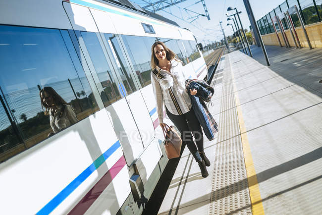 Attractive caucasian woman walking on platform next to train — Stock Photo