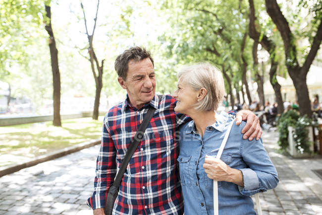 Happy cute senior couple hugging and walking together at park — Stock Photo