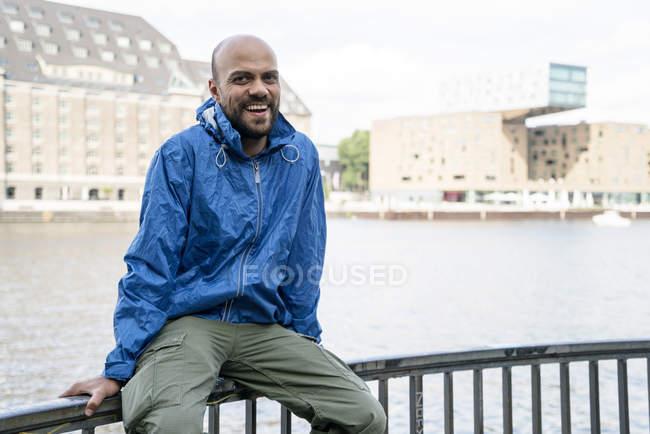Німеччина, Берлін, портрет усміхнений чоловік, одягнений синій rainjacket, сидячи на перила — стокове фото