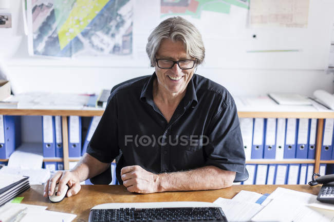 Mature man working at desk in office — Stock Photo