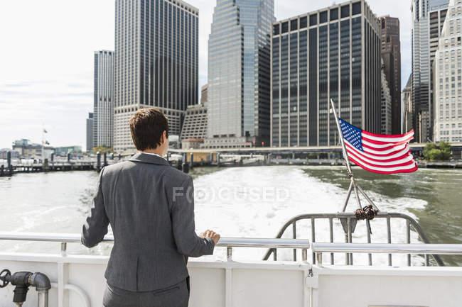 Geschäftsfrau auf dem Boot mit Blick auf Manhattan, USA, New York — Stockfoto