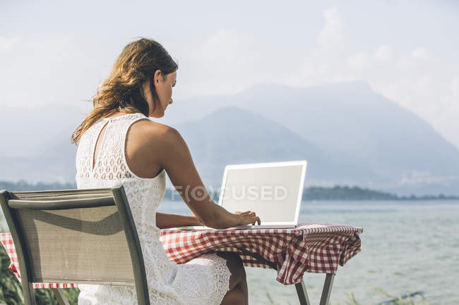 Italia, Lago di Garda, giovane donna seduta a tavola con computer portatile — Foto stock