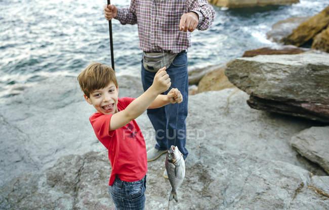 Felice ragazzo che tiene il pesce sulla lenza catturato da suo nonno — Foto stock