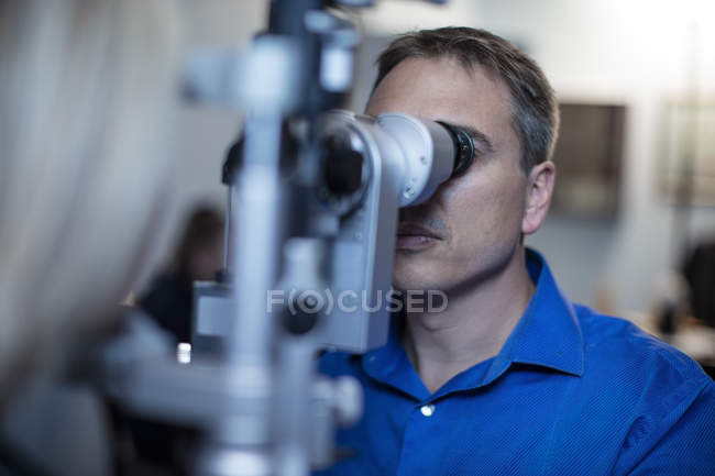 Optometrist doing eye test with patient in medical clinic — Stock Photo