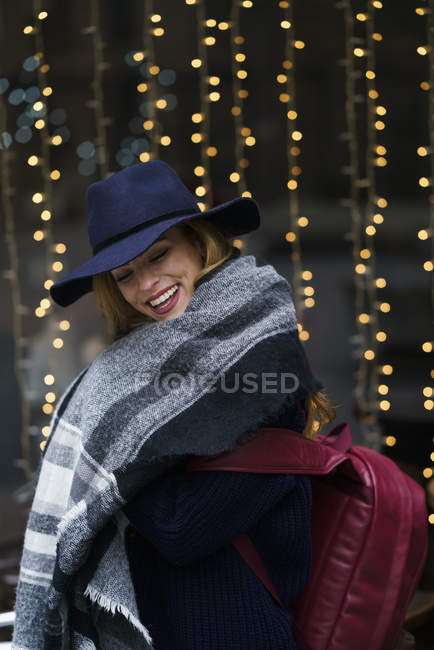 Portrait of laughing young woman wearing blue hat and scarf — Stock Photo