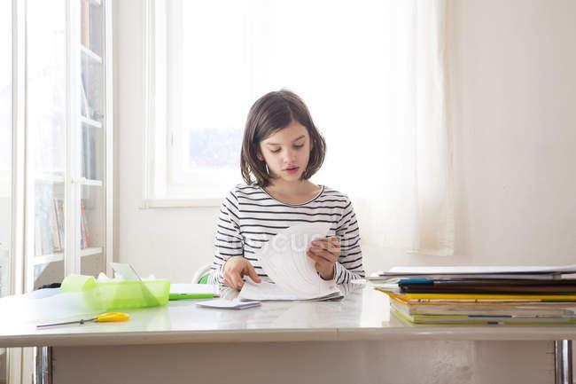 Целенаправленная девушка делает домашнее задание на столе дома — стоковое фото