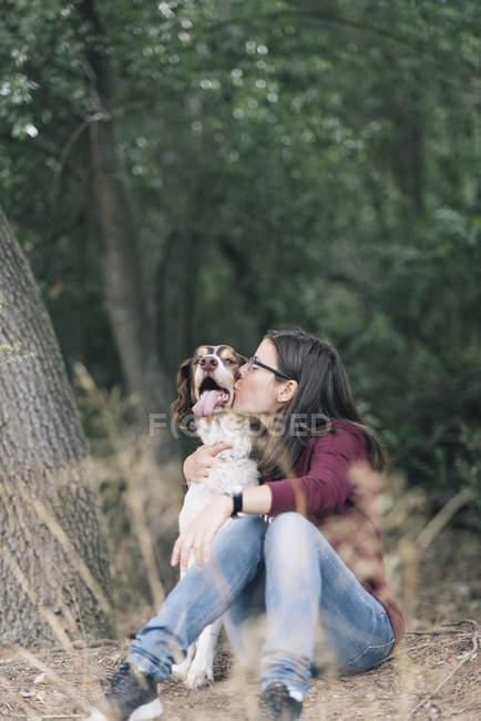 Donna seduta sul terreno della foresta e baciare il cane — Foto stock