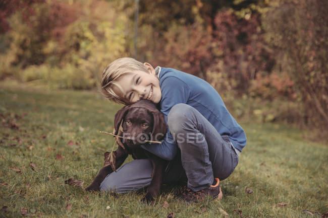 Boy hugging Labrador Retriever in garden — Stock Photo