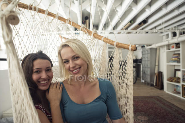 Portrait of two smiling young women in hammock — Stock Photo
