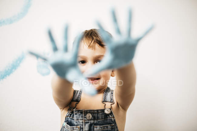 Portrait of smiling little boy showing his palms full of light blue colour — Stock Photo