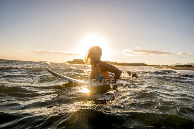 Spain, Tenerife, young female surfer in sea at sunset — Stock Photo