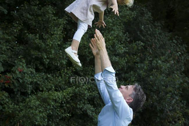 Padre buttare sua figlia in aria — Foto stock