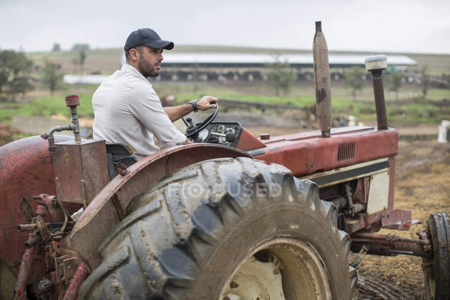 Agriculteur avec cap conduite tracteur à la ferme — Photo de stock