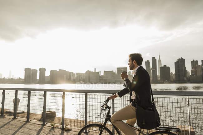 Бизнесмен на велосипеде с кофе, Нью-Йорк, США — стоковое фото