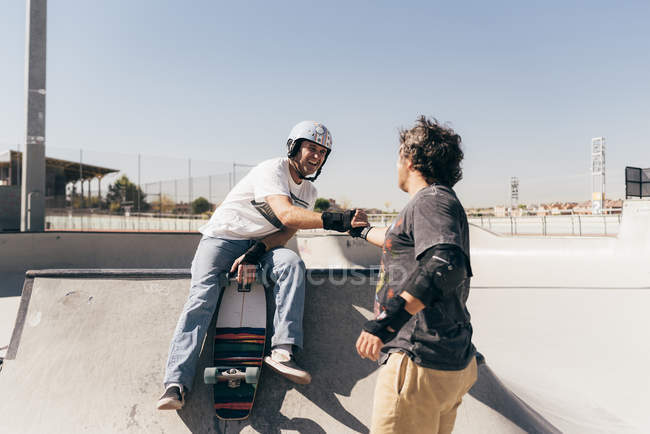 Two active men in skate park with skateboard in sunny day — Stock Photo