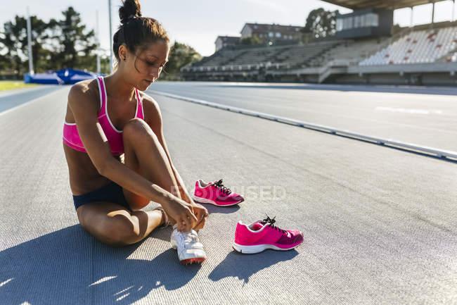 Athlète femme changer de chaussures sur la piste de course — Photo de stock