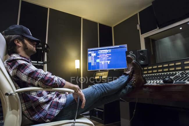Mann ruht mit den Füßen auf dem Mischpult in einem Tonstudio — Stockfoto