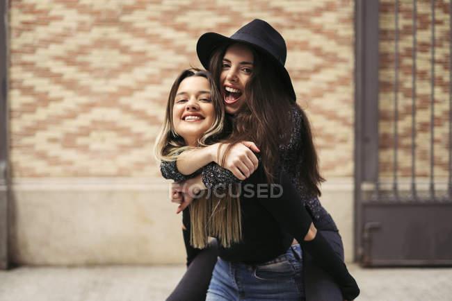 Woman giving her best a friend a piggyback ride — Stock Photo