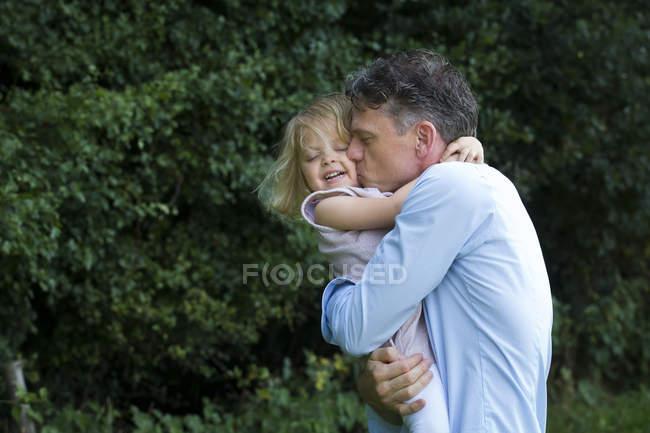 Padre abrazando a su hija - foto de stock