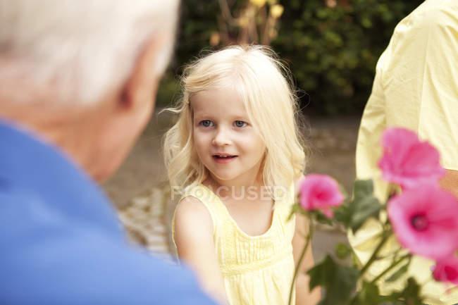 Niña con adultos mayores en el partido de jardín - foto de stock