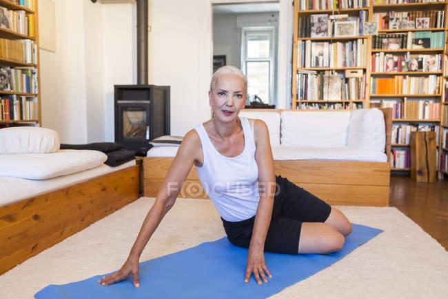 Ritratto di donna che si siede sulla stuoia di ginnastica nel salotto — Foto stock