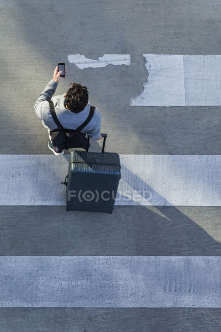 Businessman with baggage crossing the street while using cell phone — Stock Photo